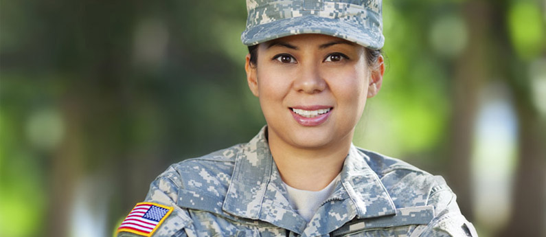 Close up of a military veteran, she is smiling and wearing her fatigues.
