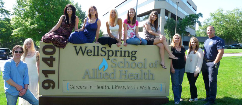 Group of students posing on and around the Wellspring Kansas Campus sign outside the school.