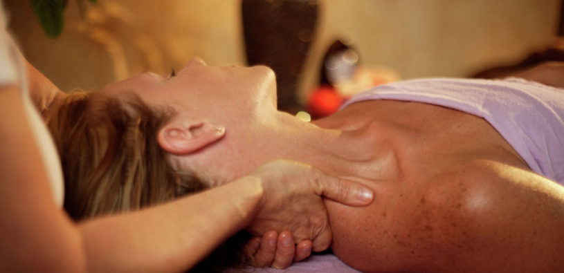 A woman gets a table massage from a massage therapist