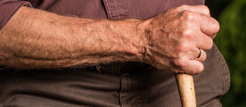 A close up image of an elderly man's arm holding a cain. Fitness trainers can share the benefits of staying active. If you're interested, call WellSpring today.