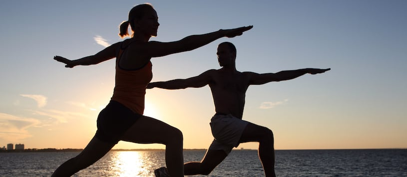 The silhouettes of two people doing yoga against a sunset