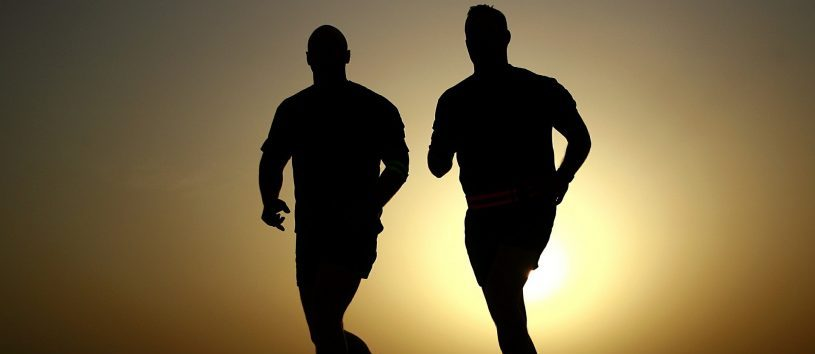 The silhouettes of two people running