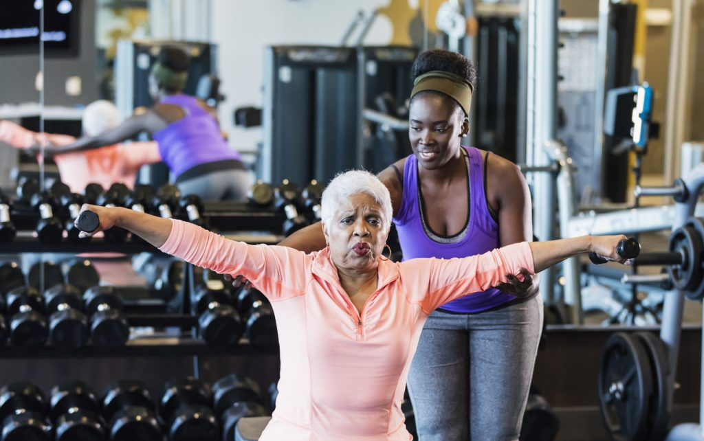 A young African-American woman in her 20s working as a personal trainer or fitness instructor in a gym. She is helping a senior African-American woman in her 60s who grimacing as she lifts hand weights.