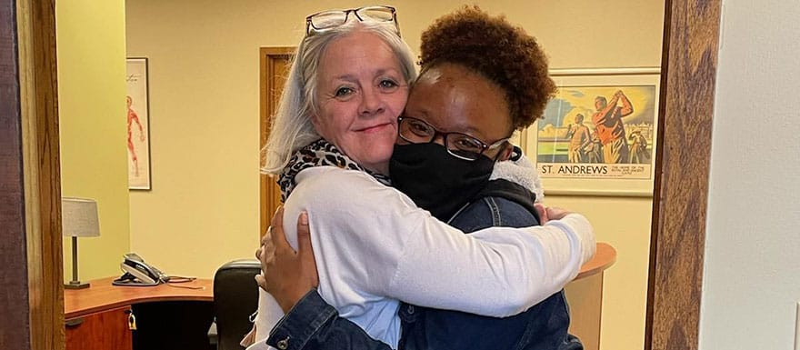 WellSpring student and staff member hugging.